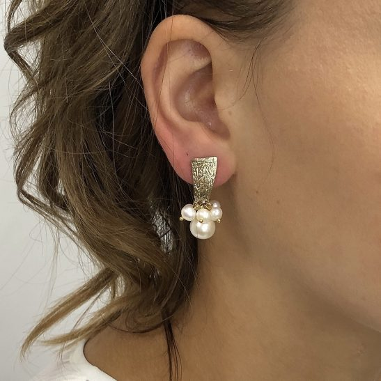 Natural Fresh Water Pearls and Gold Plated Sterling silver are the main elements feqatured in this modern but chic fashion or bridal earring. The stud is made of a gold rectangle and sterling silver post, with a small cluster of graduated freshwater pearls hang effortlessly beneath.