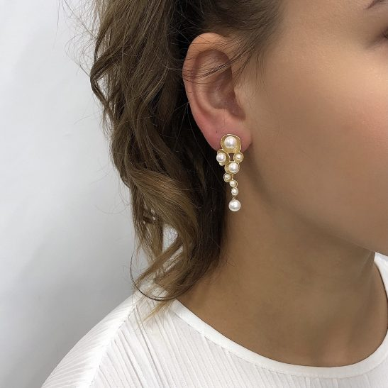 Tiny pearls are beautifly set into a rustic gold backing to create this modern bridal or fashion earring. Featuring sterling silver posts the stud design bridal earring caps the lobe of the ear perfectly cascading down the jaw line setting off chic vibes.