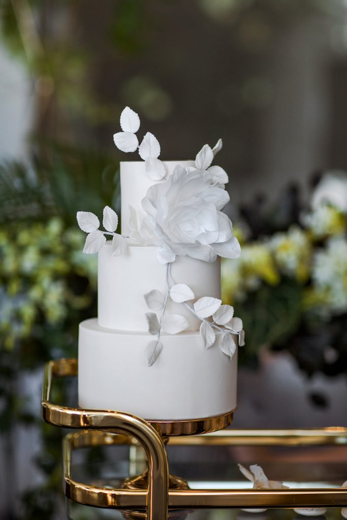 white minimal wedding cake with leafs and floral