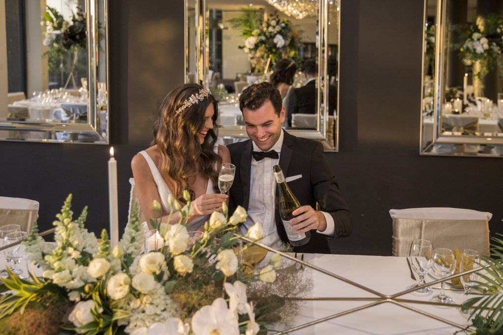 wedding image of bride and groom drinking champagne